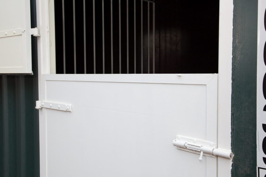 Paardenbox deur half open.